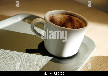 Taza de café cappuccino en bandeja en la cafetería Imagen De Stock