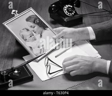 1940 del empresario manos sosteniendo una fotografía enmarcada de su esposa y su bebé en su escritorio con teléfono de papel pluma y anteojos - s9495 HAR001 HARS PAR LAS MADRES tiempo viejo nostalgia vieja fotografía Moda 1 Adultos jóvenes menores familias alegría satisfacción en el estilo de vida de mujeres casadas STUDIO SHOT cónyuge maridos vida doméstica copia espacio señoras LAS PERSONAS QUE ATIENDEN LOS HOMBRES ANTEOJOS B&W PARTNER ángulo alto su orgullo y una de las ocupaciones enmarcadas conceptual menores a mediados de adulto hombre adulto medio mamás compañerismo esposas mujer adulta joven niña EN BLANCO Y NEGRO la etnia CAUCÁSICA MANOS SÓLO HAR001 ANTICUADO Imagen De Stock