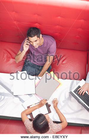 Empresario sonriente hablando por teléfono celular en la reunión Imagen De Stock