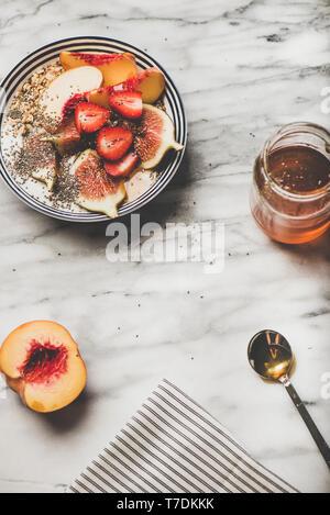 En verano el desayuno saludable. Flat-lay de yogur griego granola recipiente con fresas, higos, melocotón, semillas de chia y miel sobre fondo de mármol, superior vie Imagen De Stock