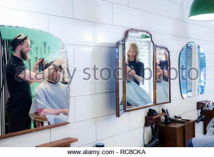 Los peluqueros corte de cabello del cliente en Gent's Barber shop Imagen De Stock