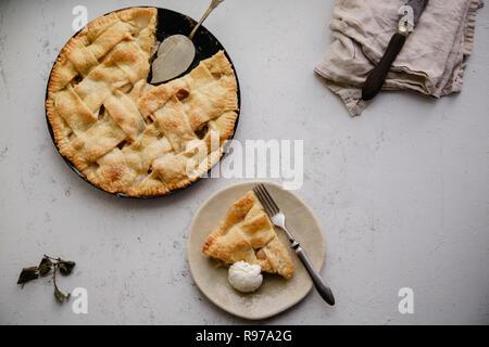Tarta de manzana con decoración de celosía y una porción servida en plato de cerámica artesanal con una bola de helado de vainilla Imagen De Stock