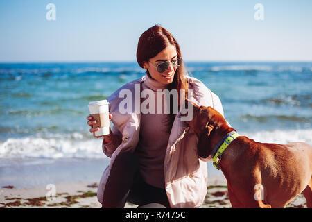 Elegante mujer adulta media en cuclillas, sobre la playa de acariciar a su perro, Odessa, Odeska Oblast, Ucrania Imagen De Stock
