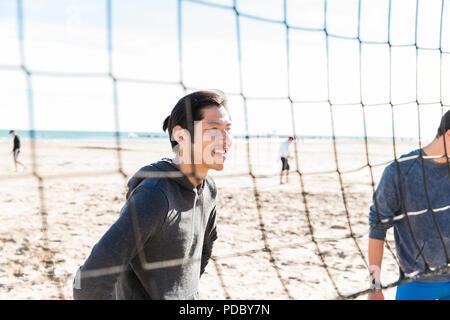 Hombre sonriente jugando voleibol de playa en sunny beach Imagen De Stock