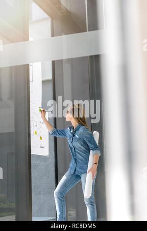 Mujer contemplando planes sobre la pared de vidrio Imagen De Stock