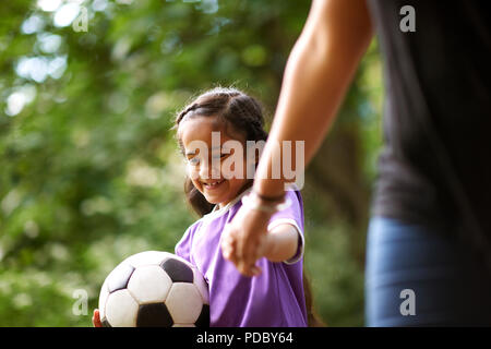 Chica sonriente con las manos la pelota de fútbol con la madre Imagen De Stock