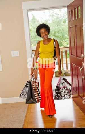Mujer en la puerta frontal con bolsas de la compra. Imagen De Stock