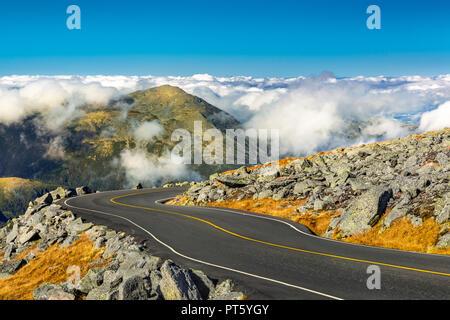 Camino sinuoso descendía del Monte Washington, NH en una soleada tarde de otoño. El Monte Jefferson pico sobresale por encima de una gruesa capa de nubes esponjosas. Imagen De Stock