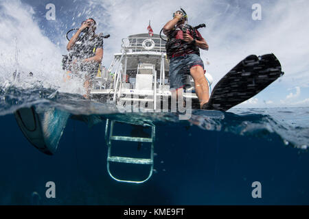 Los buzos entrar en el agua haciendo zancada gigante. Imagen De Stock