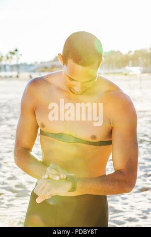 Deslizadera macho con fitness tracker control reloj de pulsera en sunny beach Imagen De Stock