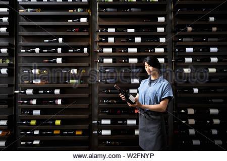 Sommelier con una botella de vino en el estante de vino en el restaurante Imagen De Stock