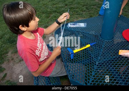 Doce años niño hispano montando un cohete modelo ajustado a disparar hacia el cielo en un parque. Imagen De Stock