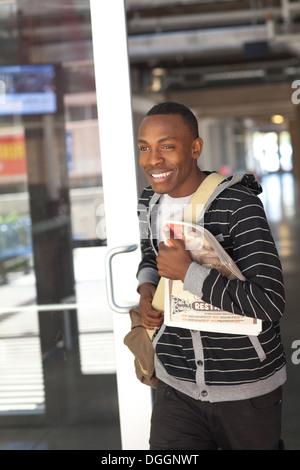 Sonriente, estudiante universitario de 18 años, camina fuera de la biblioteca universitaria con bolsa con libros y periódicos. Imagen De Stock