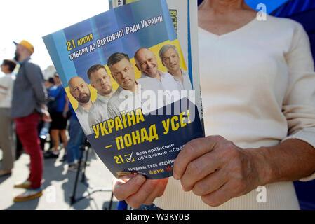 Un activista de extrema derecha Svoboda (Libertad) partido político da periódicos y folletos en Kiev.Las primeras elecciones parlamentarias tendrán lugar en Ucrania el 21 de julio de 2019. Según las encuestas de opinión, en el 2019 las elecciones parlamentarias de Ucrania 5 Partes será capaz de entrar en el Parlamento ucraniano : El presidente ucraniano Volodymyr Zelensky's partido llamado siervo del pueblo con 41,5%, pro-ruso de la oposición - Plataforma de por vida con el 12,5%, la parte de voz de estrella de rock ucraniano Svyatoslav Vakarchuk con 8,8%, solidaridad europea del ex presidente ucraniano, Petro Poroshenko w Imagen De Stock