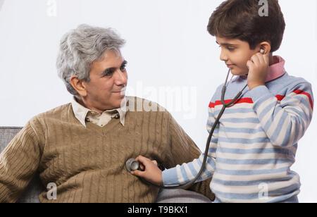Chico escuchando a los abuelos heartbeat con estetoscopio Imagen De Stock