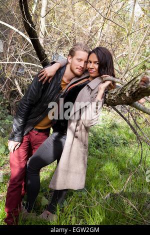 El hombre sobre la mujer inclinada contra un árbol. Imagen De Stock