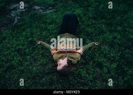 Mujer caucásica sentar en la hierba Imagen De Stock