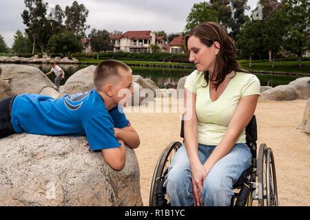 Padre en silla de ruedas hablando con su hijo tendido sobre una roca en el parque. Señor © Myrleen Pearson ...Cate Ferguson Imagen De Stock