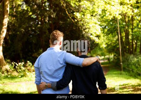 Una pareja gay masculina afectuoso abrazo, caminar en el parque soleado Imagen De Stock