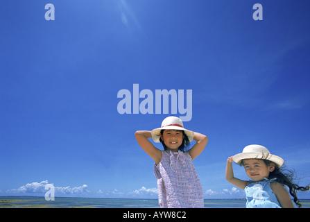 Dos niñas en el sombrero de paja Imagen De Stock