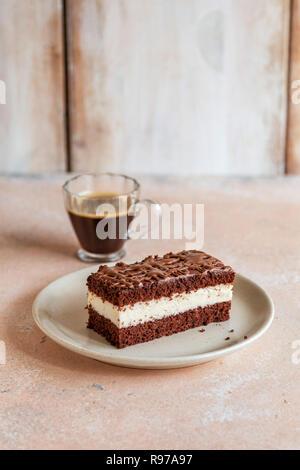 Una rebanada de pastel de chocolate y una taza de café en la mesa Imagen De Stock