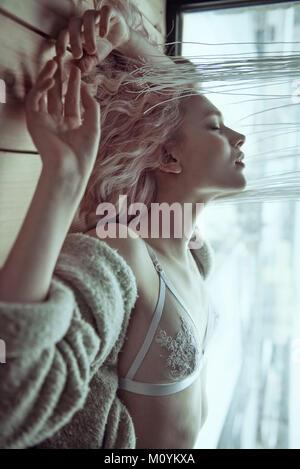 Mujer caucásica vistiendo bra acostado en el piso de madera Imagen De Stock