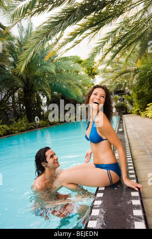 Pareja joven romancing a piscina. Imagen De Stock
