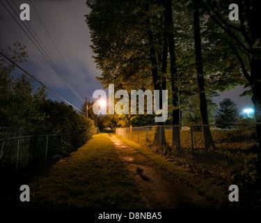 Una solitaria, desierta y espeluznante arbolados pathway durante la noche en un parque de la ciudad. Imagen De Stock