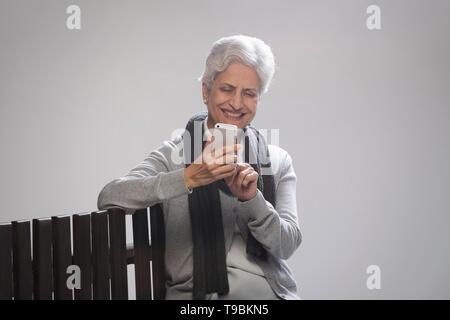 Mujer senior en ropa caliente utilizando el teléfono Imagen De Stock