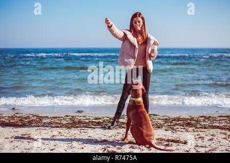 Mujer adulta media formación en la playa a su perro, Odessa, Odeska Oblast, Ucrania Imagen De Stock