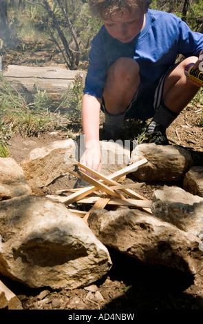 Un joven arreglando la madera para una fogata Imagen De Stock