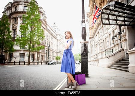 Mujer joven de pie en la calle de Londres, con bolsas de la compra. Imagen De Stock