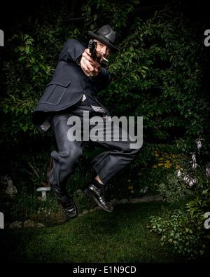 Un hombre vestido con un traje de estilo vintage y apuntar con una pistola al saltar en el aire. Imagen De Stock
