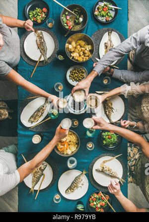 El pescado, patatas fritas, cerveza parte reunión de amigos comiendo, bebiendo y celebrando. Flat-lay de manos humanas, vasos de cerveza, lubina a la parrilla, pescados, vegetab Imagen De Stock