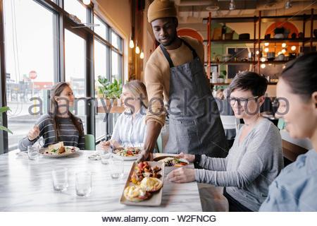 Camarero sirviendo a mujeres amigas en restaurante. Imagen De Stock