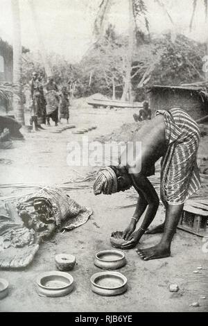 Mujer de la Costa de Oro (entonces parte del Imperio Británico), África occidental, moldeando la arcilla alrededor de un molde de piedra para hacer cerámica. Imagen De Stock