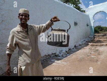 Hombre musulmán sosteniendo una enorme tetera, Región Harari, Harar, Etiopía Imagen De Stock
