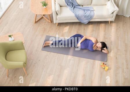 Alegre mujer embarazada para relajarse en casa Imagen De Stock