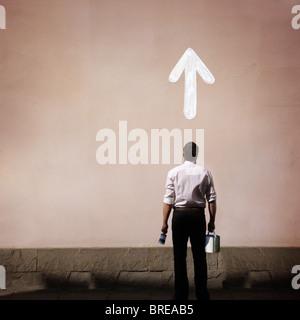 El hombre con la flecha pintada en la pared Imagen De Stock