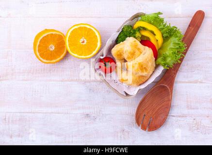 Limpiar los alimentos del desayuno croissant y ensalada sobre la mesa de madera. Imagen De Stock