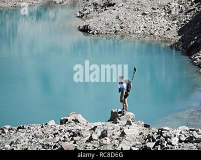 Caminante en la roca por el borde del lago, Mont Cervin, Cervino, Valais, Suiza Imagen De Stock