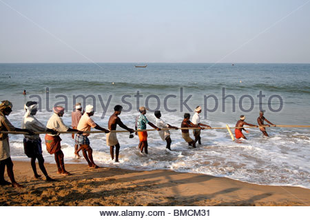 Grupo de pescadores en el trabajo en la playa Kovalam, Kerala Imagen De Stock