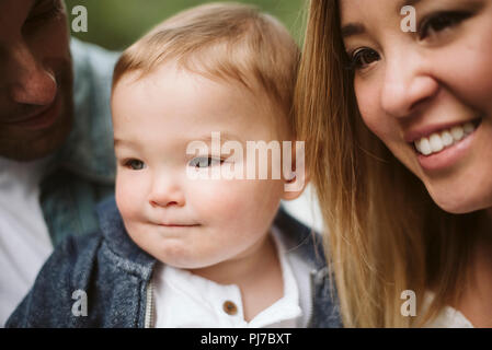 Cerca padres sonrientes y lindo hijo mirando lejos Imagen De Stock