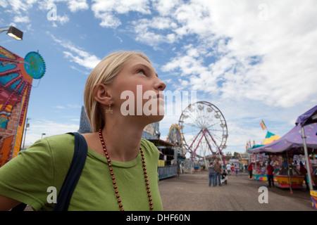 Doce años de edad, niña mira a un parque de atracciones con una expresión pensativa. Imagen De Stock