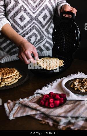 La mujer está haciendo deliciosos gofres Imagen De Stock