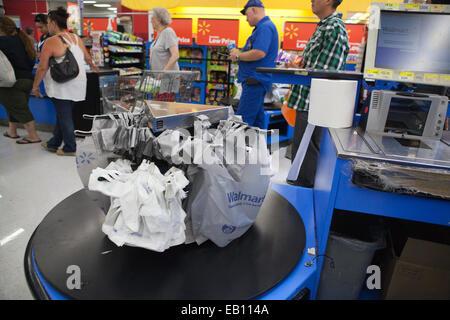 Las bolsas de plástico que cuelga en cajas registradoras, la gente espera en línea en Walmart. Imagen De Stock