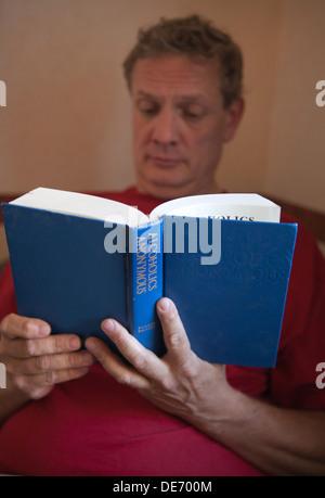 Un varón de mediana edad leyendo texto de Alcohólicos Anónimos, también llamado el Gran Libro en grupos de recuperación. Imagen De Stock