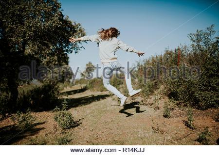 Acción de disparo un joven saltando en el aire, rodeada de árboles Imagen De Stock