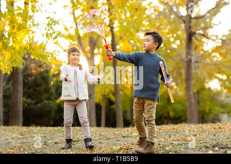 Dos niños jugando con burbujas Imagen De Stock