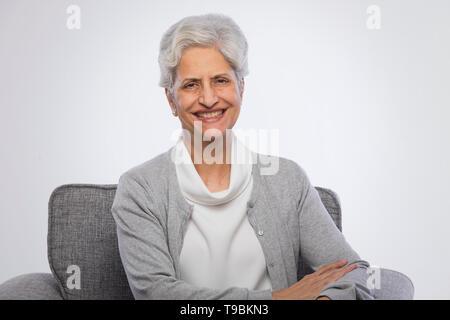 Retrato de seguros altos mujer sentada en un sofá Imagen De Stock